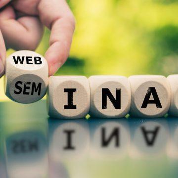 Modern Webinar or traditional Seminar? Hand turns a cube and cha